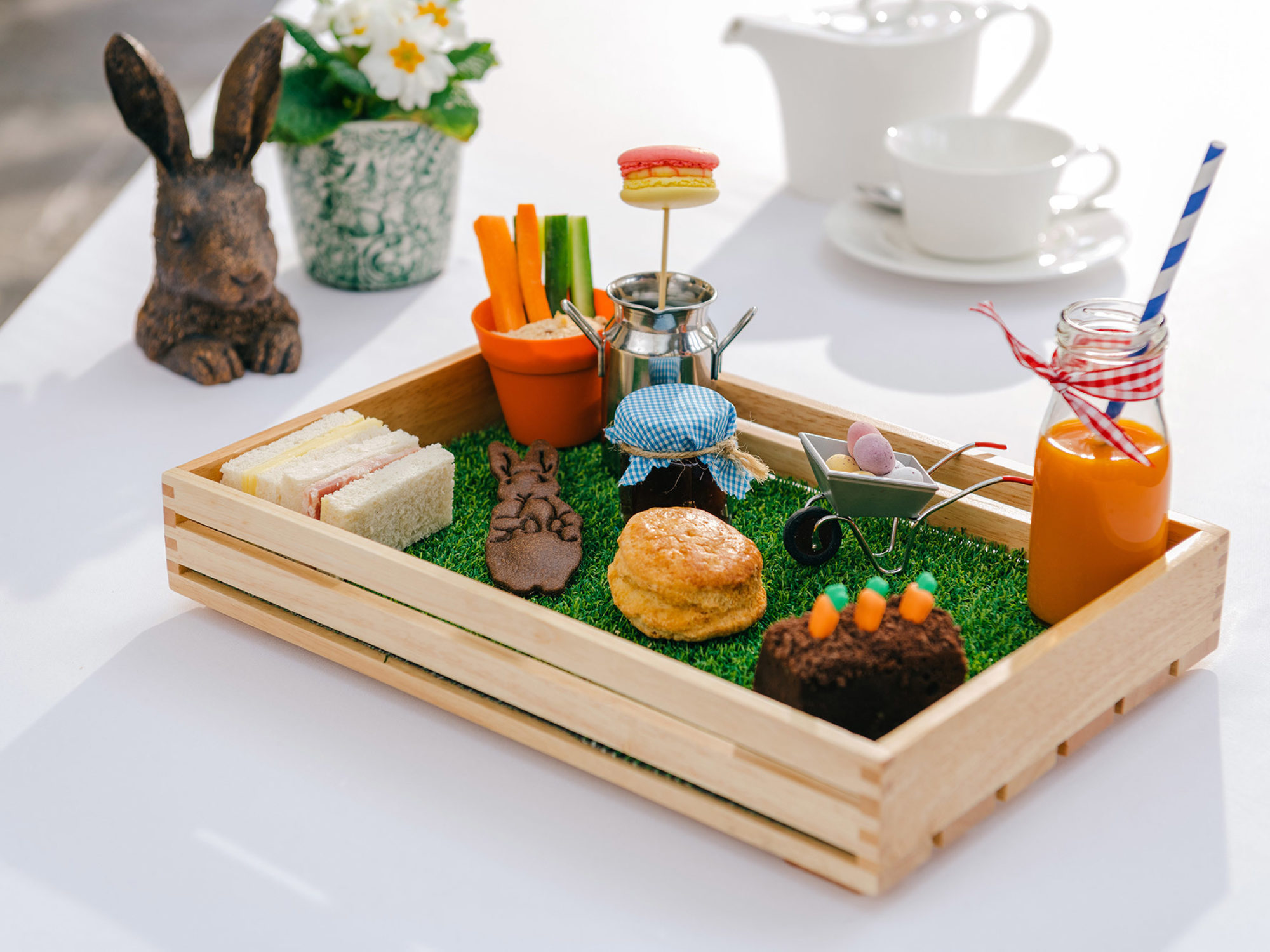 Edible garden in wooden crate with cakes and sandwiches.